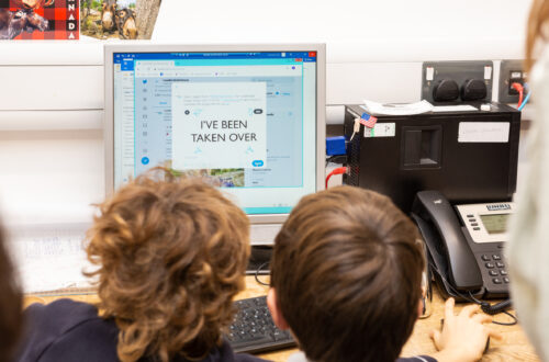 Two children sitting in front of a computer creating a Tweet for Museum Takeover Day